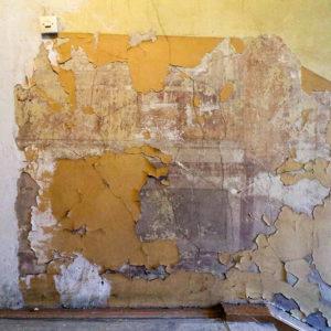 Spod łuszczącej się farby zaczynają przebijać dawne dekoracje malarskie.